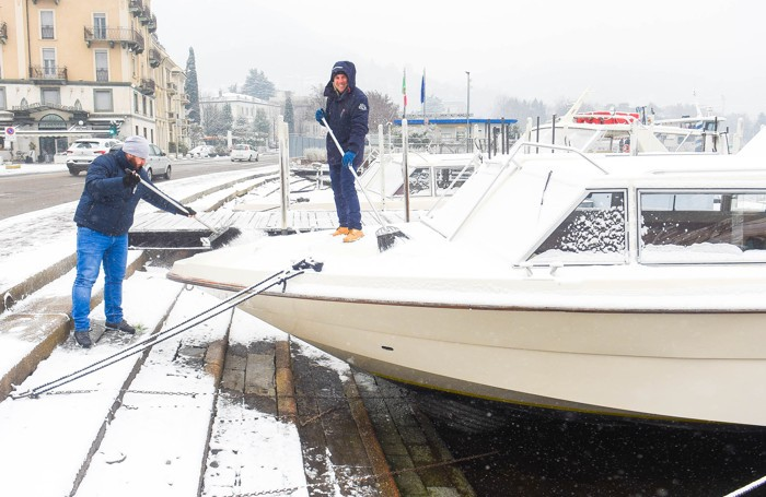 Como dipendenti del Tasell spazzano la neve dalle barche sul lungolago, nevicata