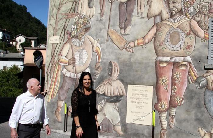 Il sindaco Ferruccio Rigola e l'assessore Lara Magoni davanti al grande graffito di Schignano