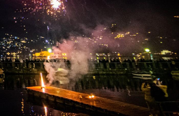 Como gente che incendia il pontile di Sant'Agostino co dei petardi durante la festa di Capodanno
