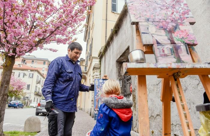 Como il pittore Camilgion Babaev dipinge con un'alunna i ciliegi di via XX Settembre