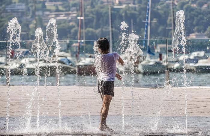 Como caldo record di quest'estate in città, bambini che si rinfrescano alla fontana della passeggiata Amici di Como