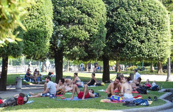Como caldo record di quest'estate in città, gente che fa il bagno e si ripara all'ombra ai giardini a lago