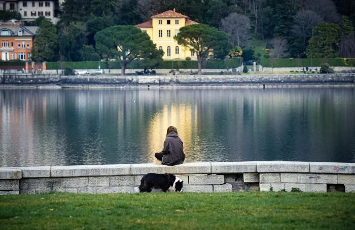 Como: gente che porta fuori il cane ai giaridini a lago domenica 15 marzo