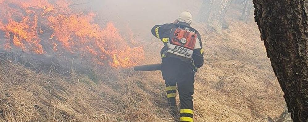 Livo, caccia ai piromani del bosco  Due elicotteri per spegnere l'incendio